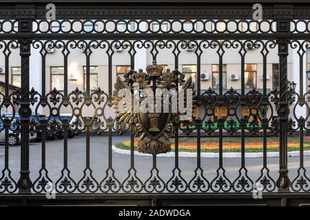 Moscow, Russia - December 01, 2019: Metal coat of arms of the Russian Federation on the black fence of the building of the Prosecutor's Office. Two-he - Stock Photo