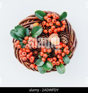 Beautiful eco friendly Christmas wreath on white background. Creative festive garland with willow and cotoneaster branches, pine cones and acorns, top - Stock Photo