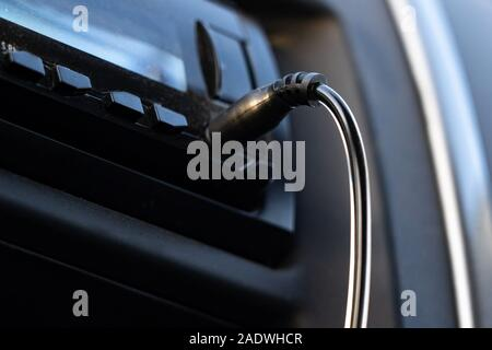 Aux cable inserting on car audio to play music from mobile phone. - Stock Photo