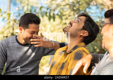 Three young adult laughing and having fun at picnic - Concept of happy friendship - youthful Male friends socializing at college.