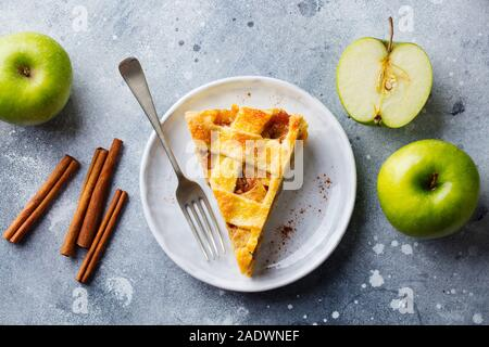 Apple pie with caramel on a white plate. Grey background. Top view