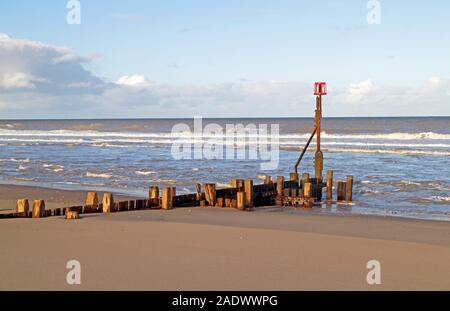 A view of a timber breakwater sea defence on the Norfolk coast at Bacton-on-Sea, Norfolk, England, United Kingdom, Europe. - Stock Photo