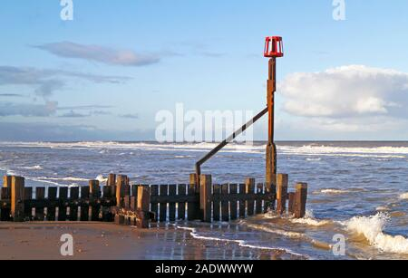 A view of the end of a timber breakwater sea defence with marker post on the Norfolk coast at Bacton-on-Sea, Norfolk, England, United Kingdom, Europe. - Stock Photo