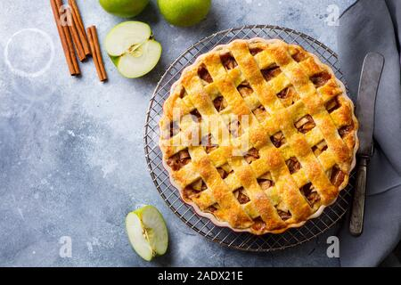 Apple pie with caramel sauce on a cooling rack. Grey background. Copy space. Top view