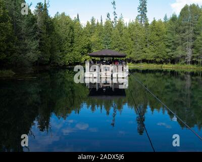 Tourists venture out on a barge to view trout in crystal clear water in Kitch-iti-kipi/Big Spring at Palms Book State Park, near Manistique, Michigan, - Stock Photo