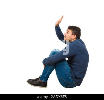 Side view scared young man introvert seated on the floor keeps hands raised to protect him from any danger, isolated over white background. Helpless g