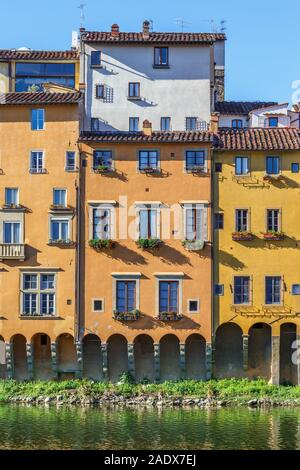 Apartment building with flower boxes along the Arno river in Florence - Stock Photo