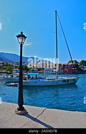 People relaxing aboard a sailing yacht, moored in the beautiful harbour of the pretty port of Assos on the west coast of Kefalonia. - Stock Photo