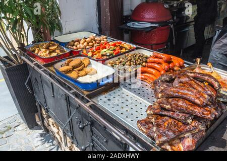 Street food on the market, in the counter they sell meat and sausages on the grill and vegetables with spices - Stock Photo