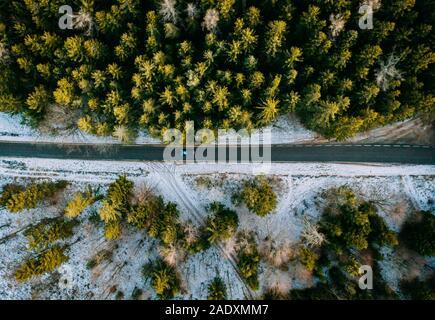 Snowy forest with a road captured from above with a drone - Stock Photo