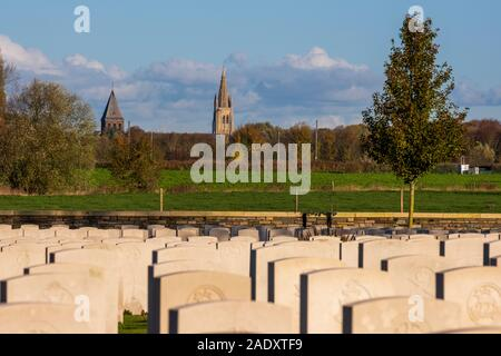 British war graves in Ypres Salient with skyline of Ypres in background - Stock Photo