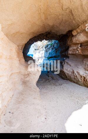 Side view on the round entrance tunnel to unique sea cave in massive rock in Tropea city near the famous Rotonda beach. Tyrrhenian sea shore in Southe