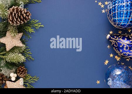 Christmas blue abstract background with blue baubles and fir branches over blue background. Christmas and New Year winter holidays greeting card - Stock Photo
