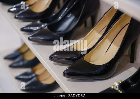 Side view of shelves of a shoe store with women's shoes on sale. Rows of new shoes in a store. - Stock Photo