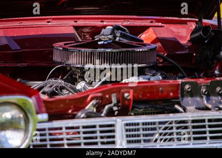 selective focus of big chromed round air intake filter on a red classic muscle car, American vehicle engine parts close up view - Stock Photo