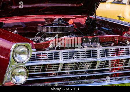 close up view of red classic muscle car front with open hood, headlight, Radiator, Chrome Bumper, big round air intake filter, and other engine parts - Stock Photo