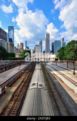 Chicago, Illinois, USA. Commuter train arriving at Van Buren Street Station with a segment of the city skyline towering above in the background.