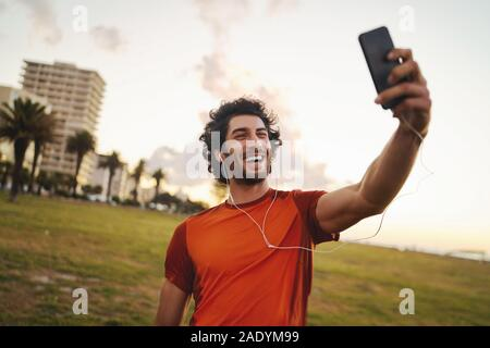 Smiling portrait of a caucasian fit young man with earphones in his ears making video call from smart phone after exercising in the park - young male