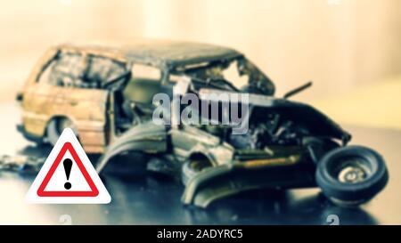 traffic accident caution sign and crashed vehicle in background - Stock Photo