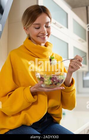Happy vegetarian kindly looking at the bowl of salad and smiling - Stock Photo