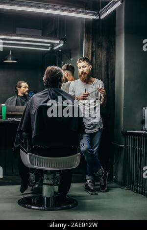 Calm barber talking to his client and looking at him - Stock Photo