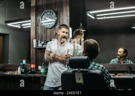 Curious barber looking at his client and talking to him - Stock Photo
