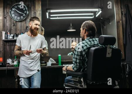 Friendly barber smiling while talking to client - Stock Photo