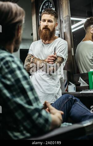 Waist up of curious barber standing and talking to client - Stock Photo