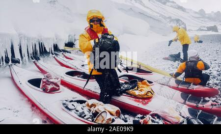 Extreme weather conditions in Antarctica as snow falls on sea kayaks, men and gear on an icy beach on the Antarctic peninsula. Brown Bluff, Antarctica - Stock Photo