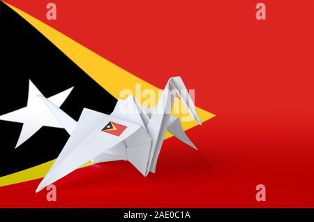 Timor Leste flag depicted on paper origami crane wing. Oriental handmade arts concept - Stock Photo
