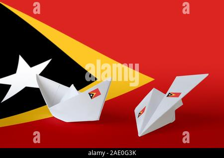 Timor Leste flag depicted on paper origami airplane and boat. Oriental handmade arts concept - Stock Photo