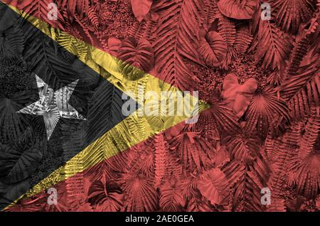 Timor Leste flag depicted on many leafs of monstera palm trees. Trendy fashionable background - Stock Photo