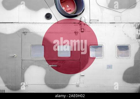 Japan flag depicted on side part of military armored helicopter close up. Army forces aircraft conceptual background - Stock Photo
