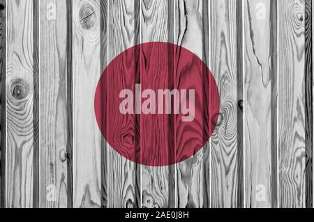Japan flag depicted in bright paint colors on old wooden wall close up. Textured banner on rough background - Stock Photo