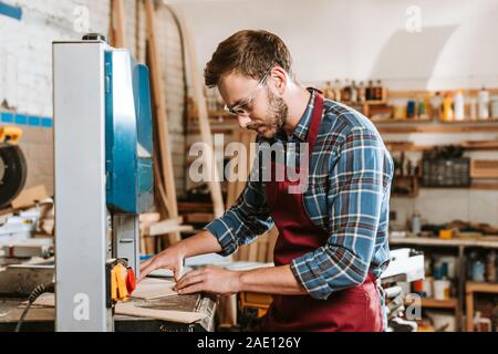selective focus of carpenter in safety glasses and apron using cnc machine - Stock Photo