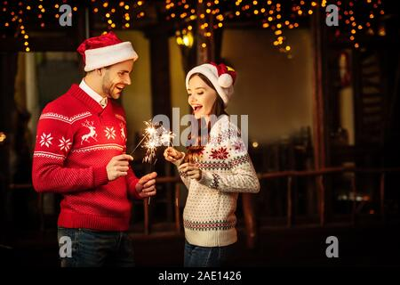 cheerful young couple in santa hats and warm sweaters holding sparklers on christmas eve - Stock Photo
