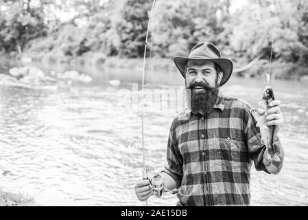 Fisher fishing equipment. Rest and recreation. Fish on hook. Brutal man stand in river water. Man bearded fisher. Fisher masculine hobby. Fishing requires to be mindful and fully present in moment. - Stock Photo