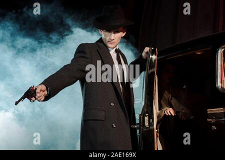 dangerous man in hat holding gun near retro car on black with smoke - Stock Photo