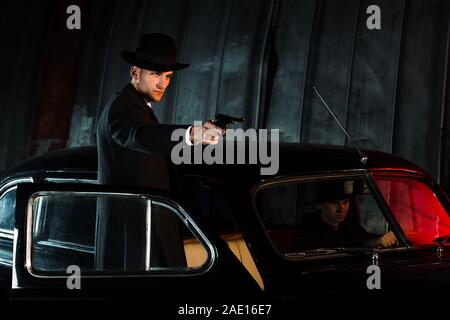 dangerous man in hat holding gun near retro car - Stock Photo