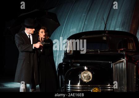dangerous man in hat holding gun and umbrella near woman and retro car - Stock Photo