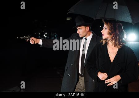 side view of dangerous man in hat holding gun near attractive girl and retro car on black - Stock Photo