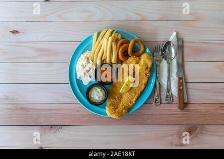 Fish & Chips with french fries, coleslaw and onion rings, western food on table concept. Flat lay top down view.