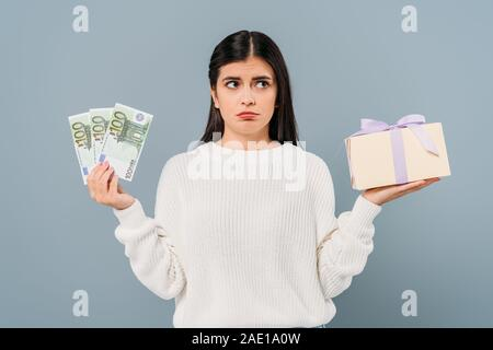 sad pretty girl in white sweater holding euro banknotes and gift box isolated on grey - Stock Photo