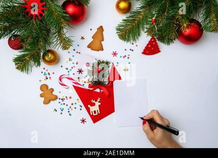 Photo of red Christmas envelope, cookies, hands with pen, branches of spruce Christmas decorations on empty white background - Stock Photo