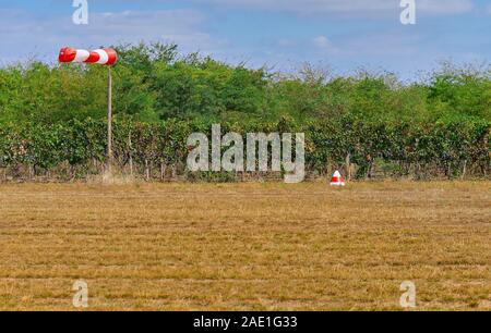 Air field direction sign and a wind force windsock against the dark blue sky, off the runway - Stock Photo