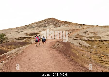 A group of hikers walking along a desert pathway with volcanic rocks and sand dunes in Madeira Island (Ponta de Sao Lourenco, Portugal, Europe)