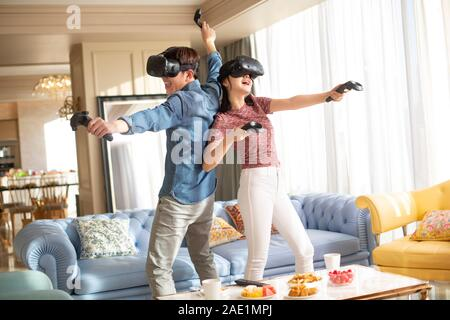 Young couple playing VR game - Stock Photo