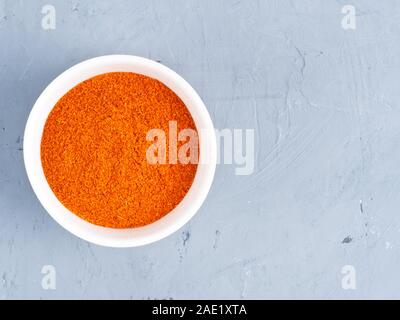 Ground red chili pepper in a white bowl on a gray concrete background. Healthy eating concept - Stock Photo