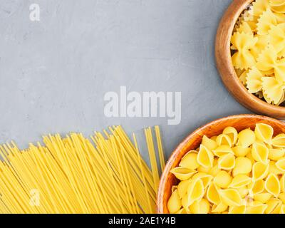 Different types of pasta in wooden bowls and on a gray concrete background with copy space. Healthy eating concept - Stock Photo