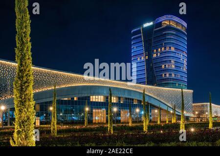 Tashkent, Uzbekistan - 30 October, 2019: Congress hall and Hilton hotel with colorful illumination at night in Tashkent City Park - Stock Photo